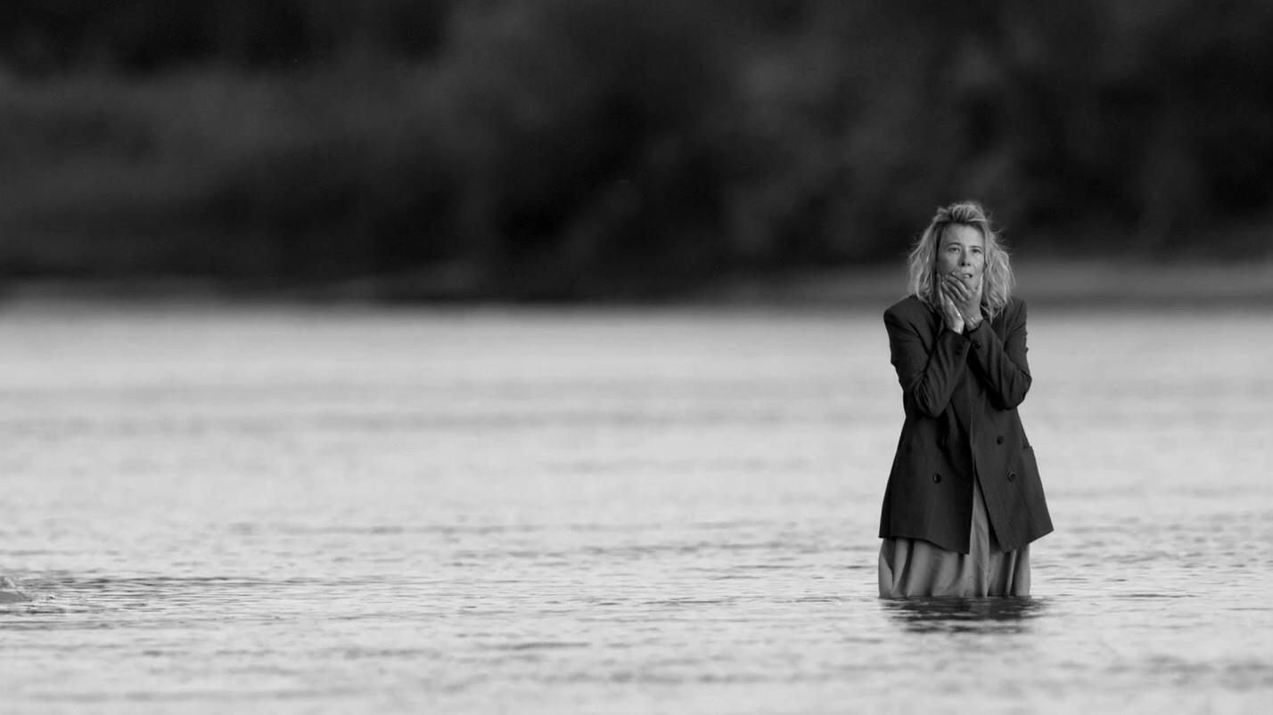 cena do filme Caros Camaradas! em branco e preto em que a personagem Lyuda aparece no meio de um rio, com a água batendo nas pernas. Ela aparece com o cabelo loiro desgrenhado, o olhar aflito, as mãos sujas sobre a boca, vestindo uma jaqueta escura.