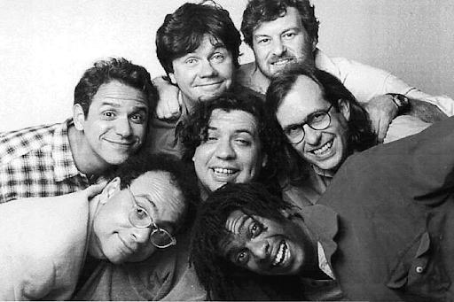 Imagem dos sete integrantes do grupo Casseta e Planeta em preto e branco. Eles estão amontoados, se abraçando e sorrindo para a câmera.