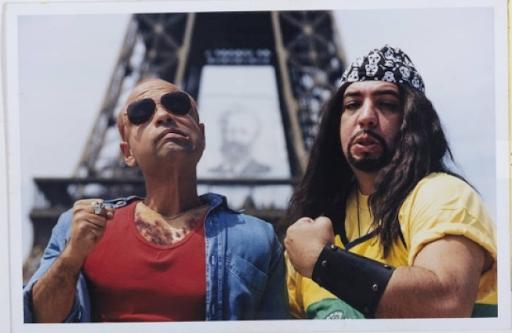 """A foto exibe Cláudio Manoel e Bussunda posando em frente da Torre Eiffel. Cláudio é um rapaz baixinho, negro e careca. Cláudio está ao lado esquerdo da imagem, vestindo camiseta de gola """"v"""" vermelha e uma camisa jeans azul. Ao lado direito temos Bussunda com uma camiseta amarela, fazendo um gesto de punho cerrado típico do movimento punk-rock."""