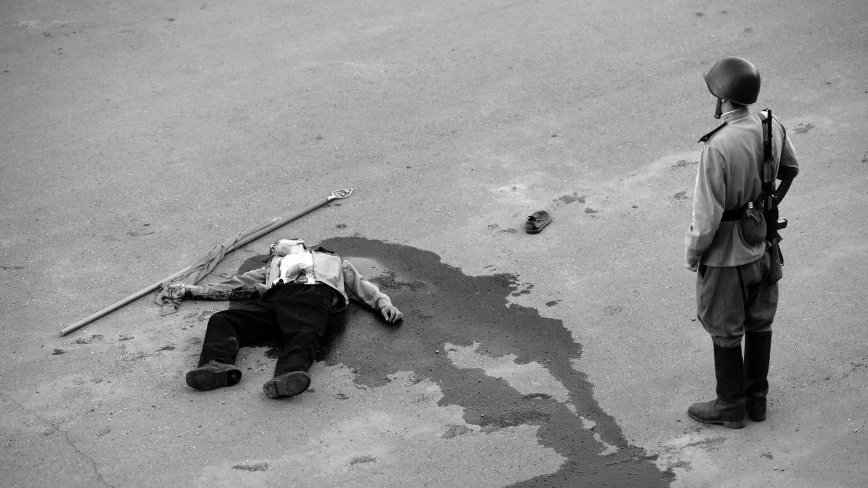 cena do filme Caros Camaradas! em branco e preto que mostra um homem morto baleado no chão, com o sangue escorrendo ao seu redor e uma bandeira perto de sua mão. No canto direito está um soldado de costas para a imagem vestindo a farda do exército e olhando para o homem baleado no chão.