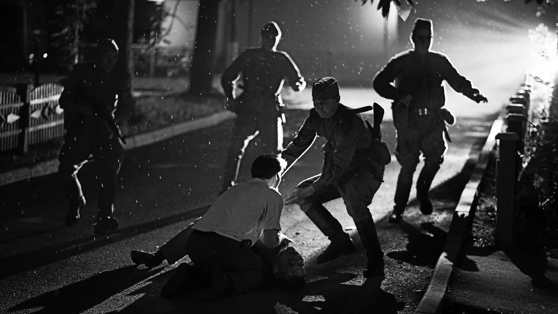 cena do filme Caros Camaradas! em branco e preto em que um homem tenta salvar outro ferido. Ao redor estão quatro soldados, que correm em direção aos protestante no chão.