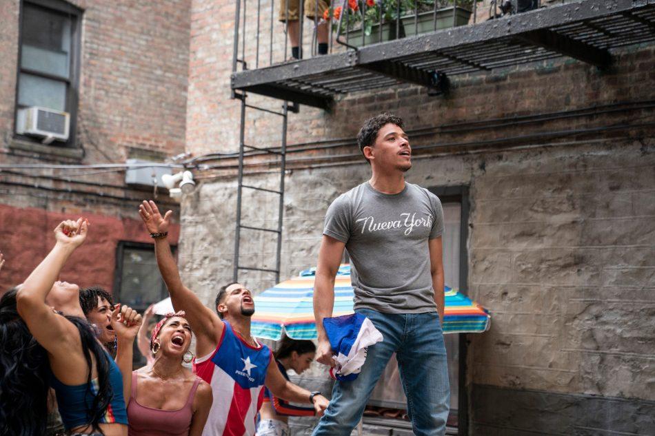 Cena do Filme Em Um Bairro de Nova York. A imagem mostra, de lado, um grupo de pessoas latinas dançando na rua, na frente de um prédio de tijolos cinzas. Eles olham para a frente, no lado direito da imagem. Á frente do grupo está o personagem Usnavi, de Anthony Ramos, um homem jovem latino, de cabelos curtos castanhos. Ele está de pé, cantando, e usa uma camisa cinza escrito 'Nueva York' e calça jeans. É de dia e a imagem é iluminada.