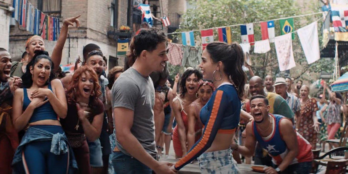Cena do filme Em um Bairro de Nova York. Anthony Ramos e Melissa Barrera estão no centro da imagem, de mãos dadas e olhando um para o outro. Ambos são latinos de pele clara com cabelos escuros. Ao fundo, muitas pessoas exibem expressões de animação.