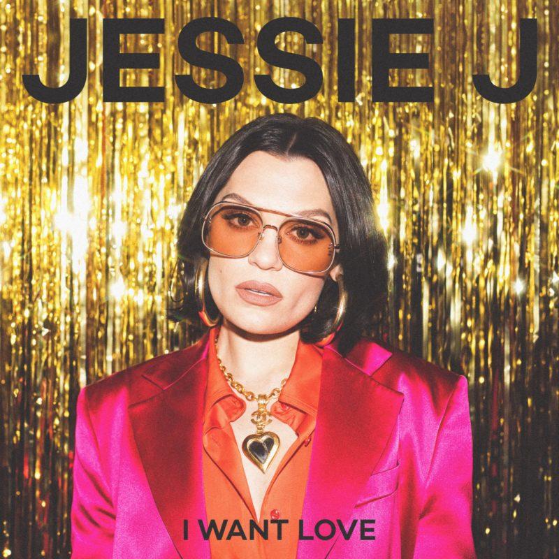 Capa do single I Want Love, de Jessie J. A cantora está num fundo dourado, usando um óculos rosa e um terno rosa. Ela usa também um cabelo preto curto chanel.