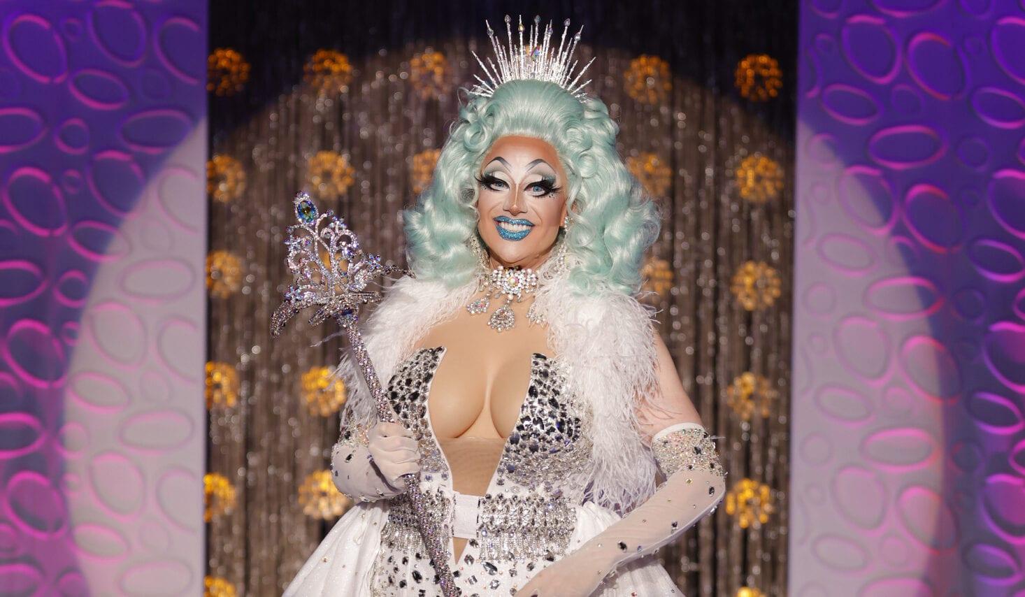 Cena de Drag Race Down Under. Nela, vemos Kita Mean, uma drag queen branca e de peruca azul claro, com peitos falsos e um vestido branco, segurando um cetro e com uma coroa na cabeça.