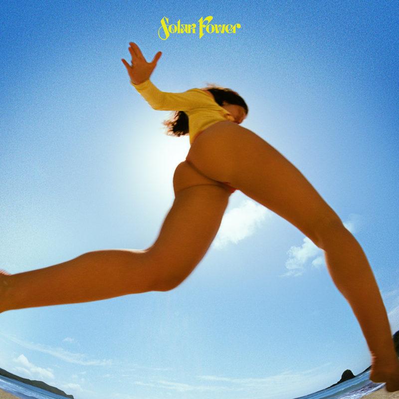 Capa do single Solar Power, de Lorde. A foto foi tirada de baixo, enquanto a cantora pulava por cima da câmera. Ela está sem calças, e usa um maiô de manga comprida amarelo. Acima da cantora, há um céu azul, e um sol que se esconde atrás dela. Ela está na praia.