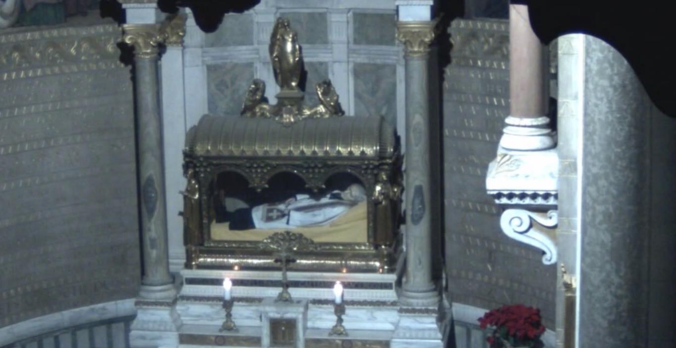 Cena do filme Natalis apresenta uma igreja com um santo dentro de uma redoma de vidro e metal, usando uma batina branca e uma estola vermelha. Na frente da cúpula está uma cruz pequena de metal, duas velas e duas colunas na lateral.
