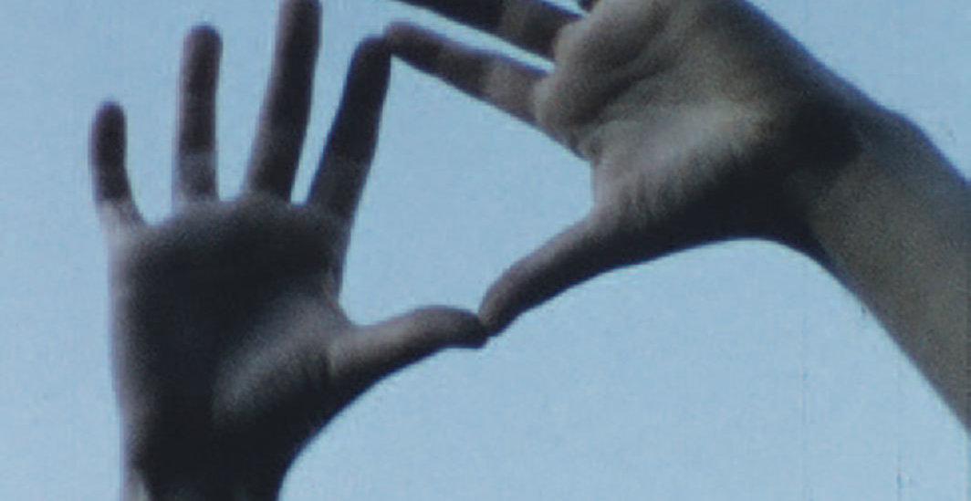 Cena do filme O Céu Socialista que exibe duas mãos de uma pessoa branca unindo os indicadores e o polar para formar um triângulo. Ao fundo é possível ver o céu azul.