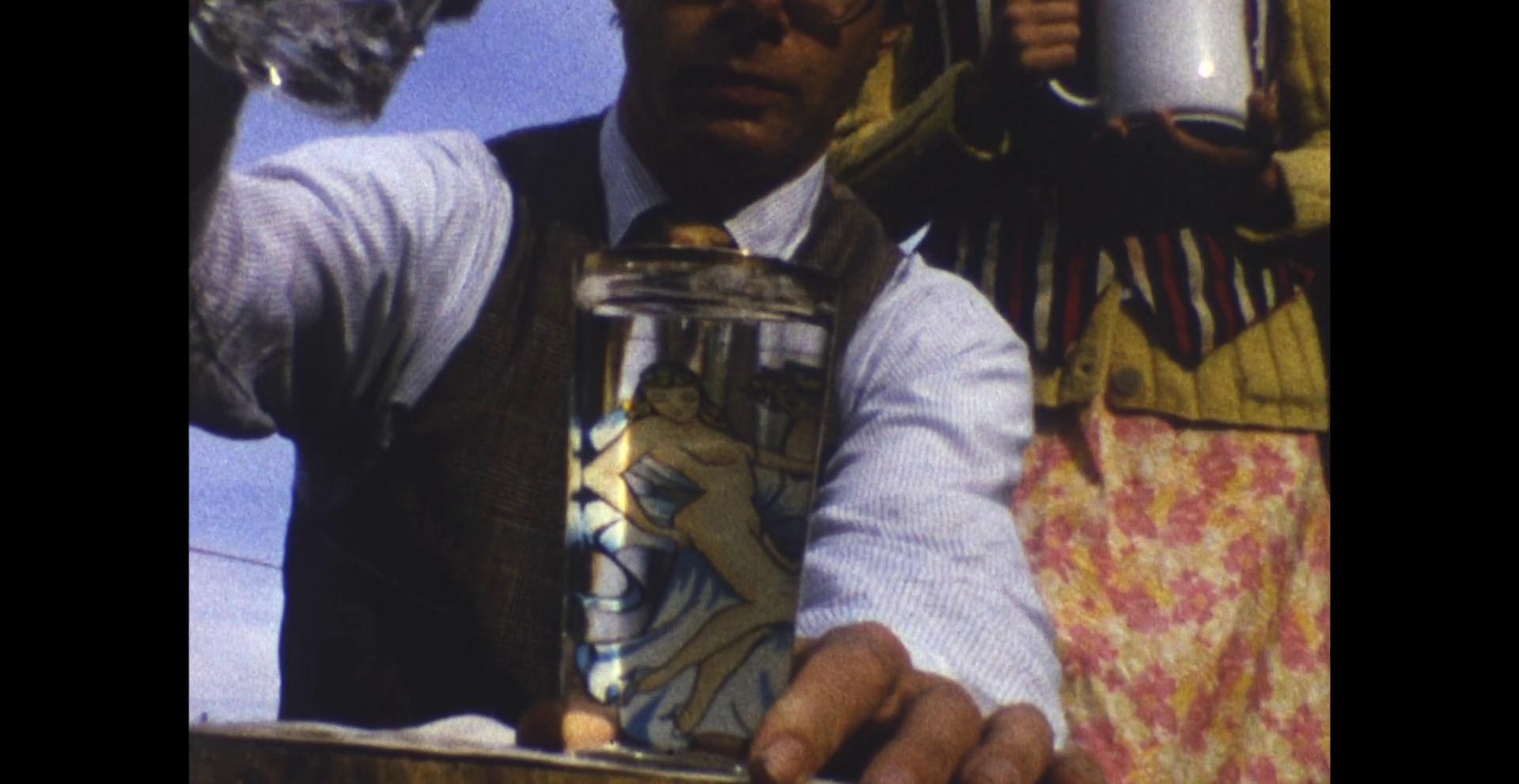 Cena do filme O Céu Socialista: Arredores e Outtakes em que aparece um homem, usando camisa social branca, colete e gravata, preenchendo um copo, com desenho de uma mulher nua, com água. Em segundo plano, está uma mulher de jaqueta amarela e saia florida segurando uma jarra branca.