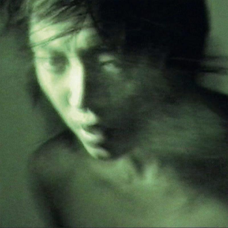 Capa do disco Jade 玉观音, da cantora Pan Daijing. A capa é uma foto de uma pessoa asiática, assustada e desfocada, e a capa é verde