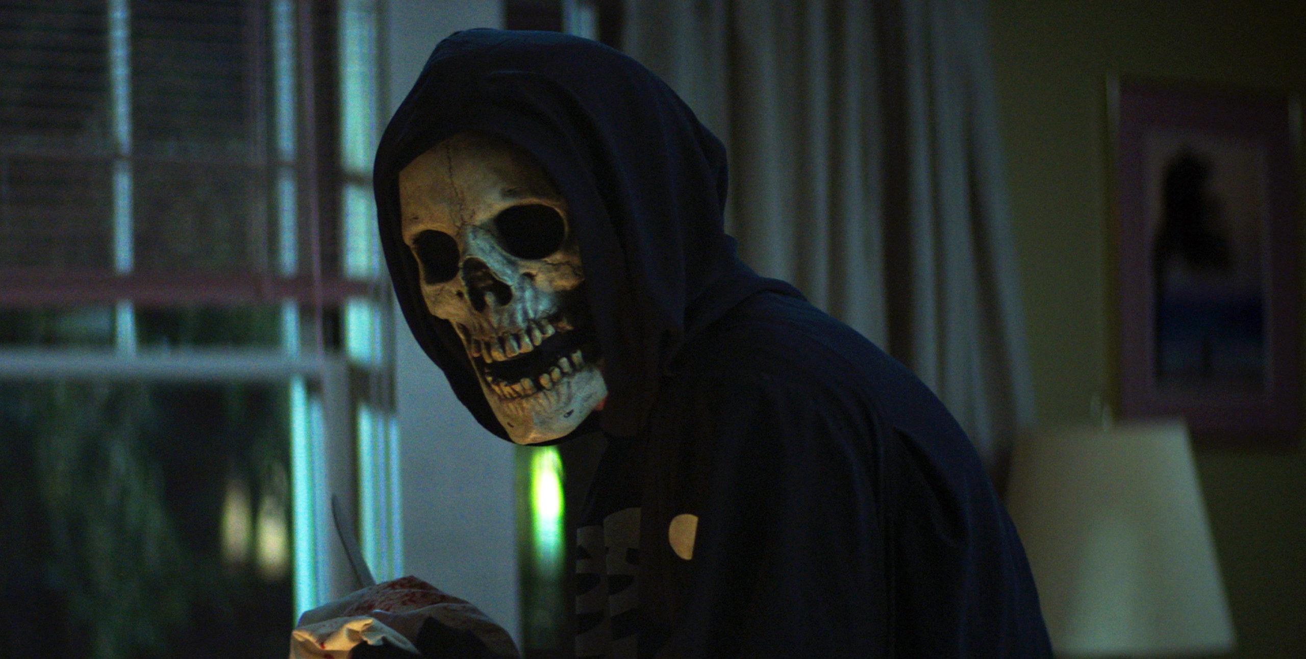 Imagem do filme Rua do Medo: 1994 - Parte 1. Na imagem vemos uma pessoa fantasiada com uma mascara de caveira e uma roupa preta com capuz. Ao fundo, vemos uma janela aberta e suas cortinas ao lado, como também um quadro rosa com uma imagem.