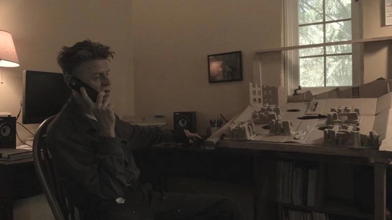 Cena do curta Restos e Memórias de Filmagem exibe um homem de sessenta anos sentado em uma cadeira enquanto fala ao telefone. À sua frente, vemos a maquete de uma cidade em cima de uma escrivaninha e atrás dele vemos o monitor de um computador e as caixas de som.
