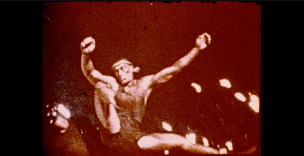 Cena de Senhor Jean-Claude exibe uma foto antiga do ator usando uma faixa na cabeça e pulando, prestes a dar um chute em alguém.