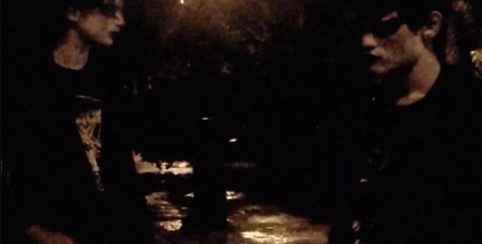 Cena do filme Sombra exibe dois rapazes vestidos somente com roupas pretas. Usam maquiagem branca e preta ao redor dos olhos. Um está de frente para o outro em uma praça, durante a noite.