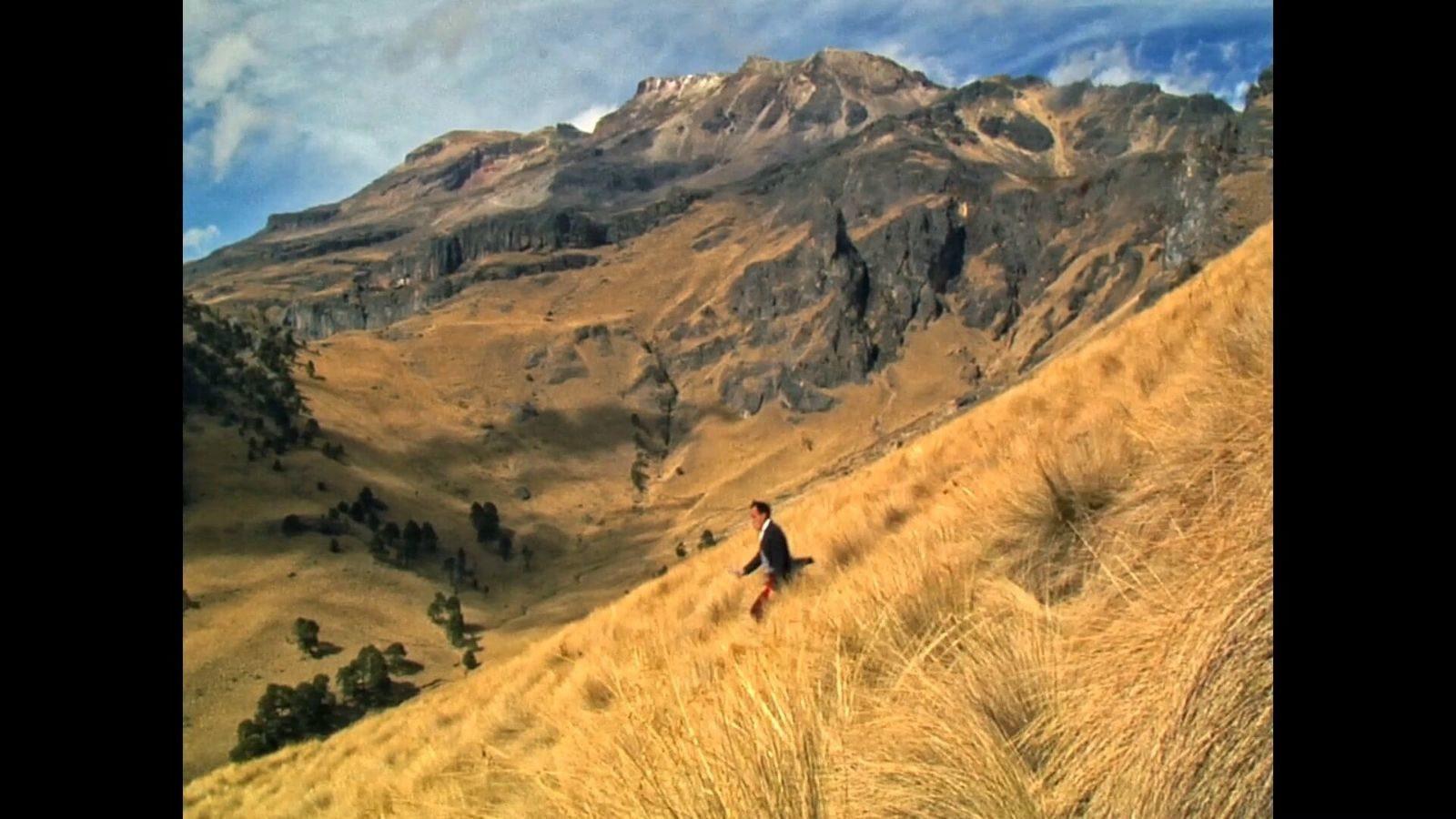 Cena do filme Toda Luz Que Podemos Ver exibe uma paisagem com vegetação rasteira e seca, montanhas ao fundo e o céu azul com poucas nuvens. Ao centro da imagem aparece um homem de roupa preta andando pela vegetação baixa.