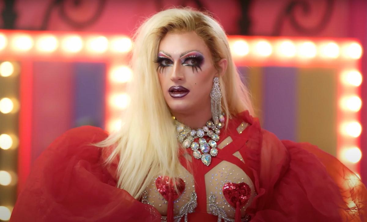 Cena de Drag Race Down Under, em um close-up da drag queen Elektra Shock, que é loira, usa uma roupa vermelha com corações no lugar dos seios e longos cílios escuros.