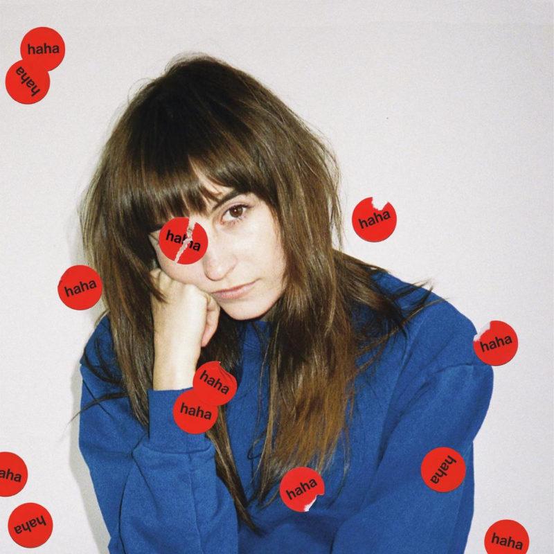 Capa do CD I Know I'm Funny haha, da cantora Faye Webster. A capa mostra uma foto dela, branca e de cabelos pretos e casaco azul, com a mão no rosto e olhando para a câmera. A capa tem vários adesivos redondos vermelhos, escrito haha