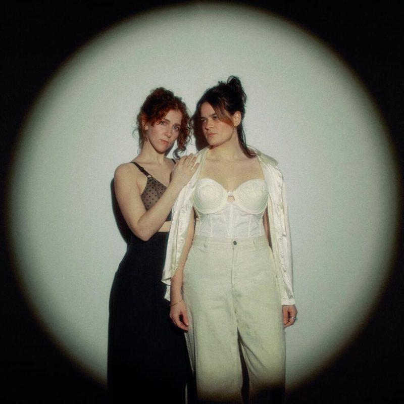Capa do EP Used To Be Scared Of The Dark, do duo Overcoats. A foto mostra as duas cantoras, no escuro mas iluminadas por um holofote redondo. O fundo iluminado é branco.