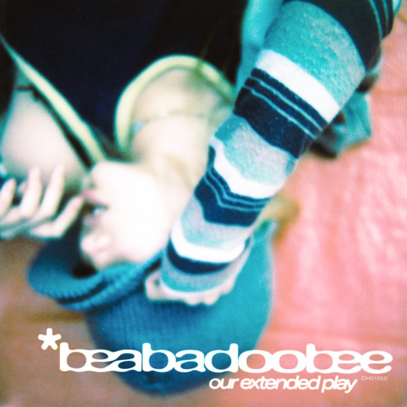 Capa do EP Our Extended Play EP, da cantora beabadoobee. A foto mostra ela, de touca e roupa de frio, de ponta-cabeça, com a mão no rosto e o nome do registro escrito em fonte branca, abaixo do nome dela, escrito em fonte maior.