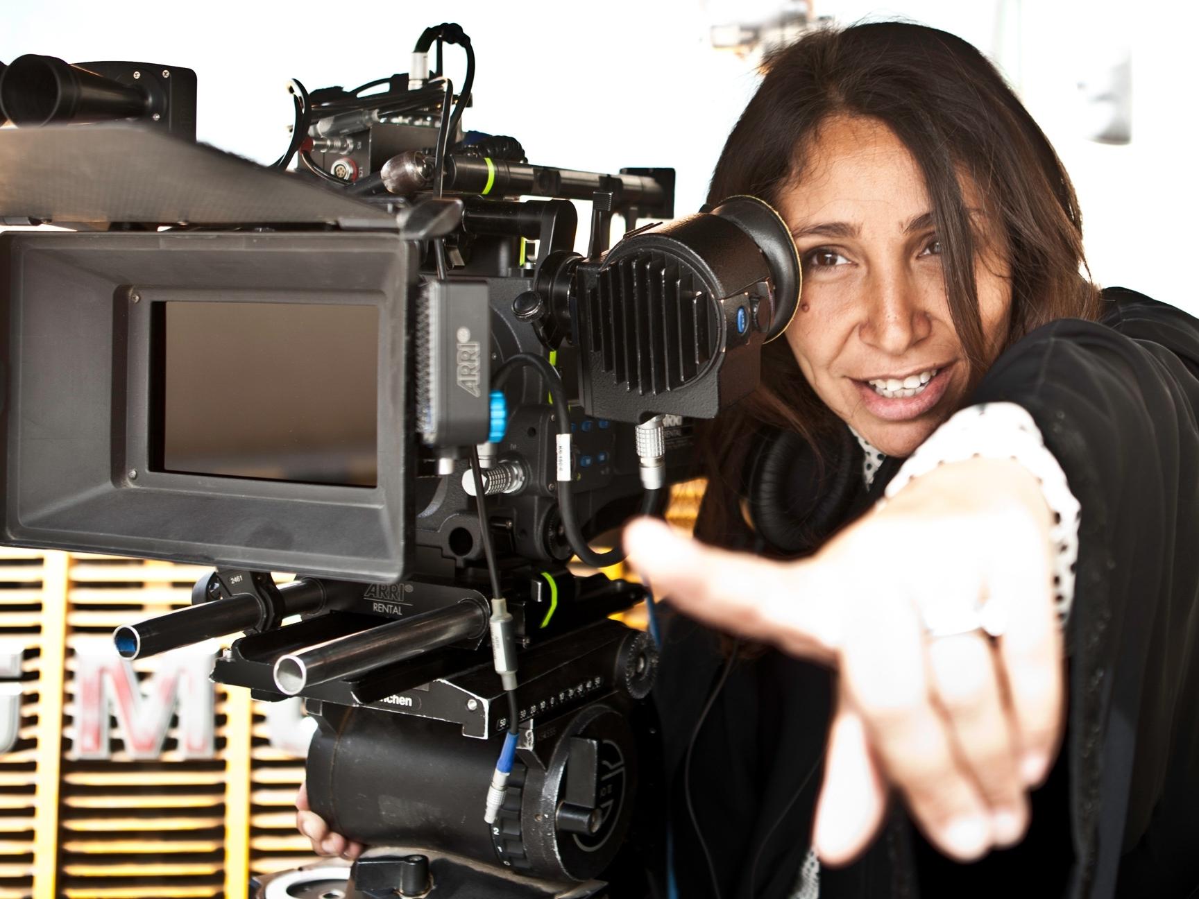 Foto da diretora Haifaa Al-Mansour. A mulher marrom de cabelo liso castanho está sorrindo com uma mão apontada para frente. A sua esquerda está uma grande câmera. No fundo é possível ver um painel de madeira com letras penduradas.