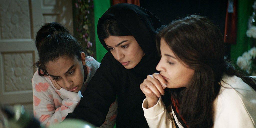 Cena de A Candidata Perfeita. Nele estão três as mulheres protagonistas olhando para a tela de um computador com as expressões sérias. A do meio veste roupa e hijab preto enquanto as dos lados estão de roupas rosas claras.