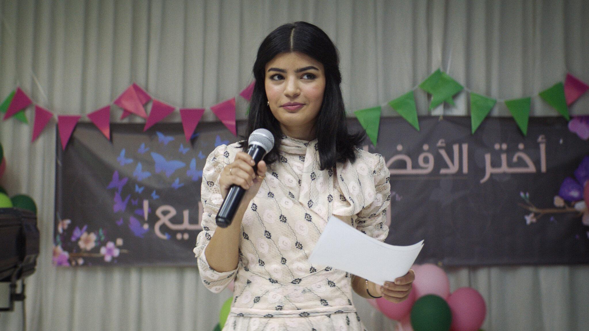 Cena do filme A Candidata Perfeita. Nela está a protagonista em pé, usando um vestido rosa com estampa e segurando um microfone. Seu cabelo está com a parte da frente presa. O fundo é uma parede branca decorada com bandeiras rosas e verdes, além de uma placa preta.