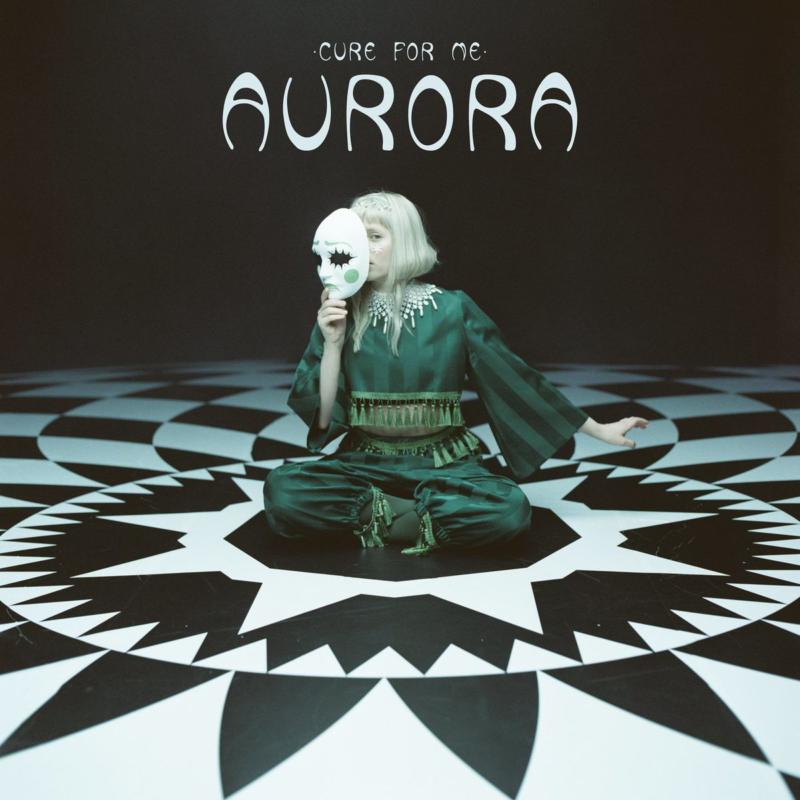 Capa de Cure For Me de AURORA. No centro de uma sala escura, com o chão formado de formatos pretos e brancos, está AURORA. A cantora veste um conjunto verde escuro formado por calça e blusa de manga. Ela está sentada no chão com uma máscara cobrindo parte do seu rosto de pele clara e cabelo loiro. A máscara é branca com detalhes em verde. Na parte superior da arte está o nome da música e da cantora, ambos em branco.