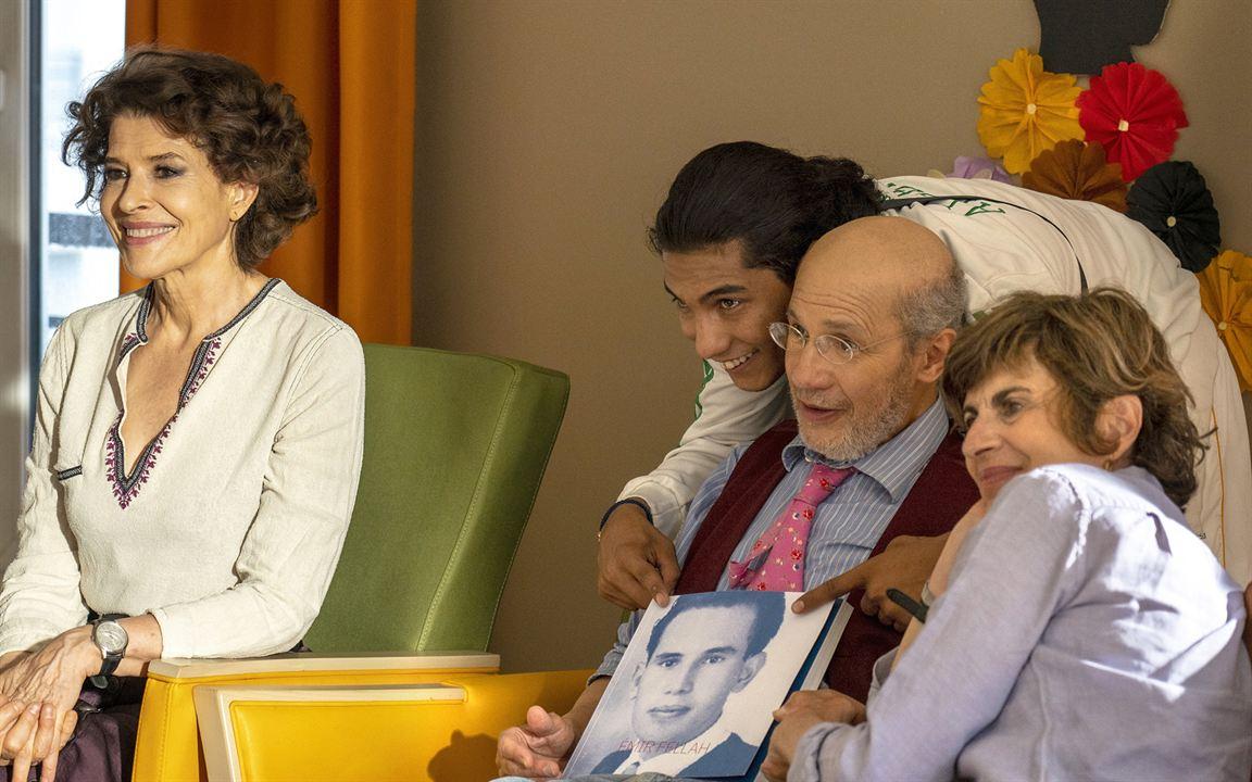 Cena do filme DNA. A imagem mostra parte de uma família ao redor de um senhor numa sala de casa de repouso. A imagem os mostra de lado, e eles estão olhando para a frente, posando para uma foto. No lado esquerdo da imagem está uma mulher de meia idade sentada numa cadeira verde pistache com as mãos sobre os joelhos. Ela tem os cabelos castanhos curtos ondulados e usa uma bata branca com detalhes roxos, sorrindo para a frente. Ao lado dela, está um senhor de idade, sentado numa cadeira amarela. Ele tem barba e cabelos brancos, usa um óculos, camisa listrada azul, uma gravata rosa e um cardigã vermelho escuro. O senhor segura uma fotografia antiga em cima do colo, que mostra o rosto de um homem jovem em preto e branco. Atrás dele, abraçando-o por trás, está um jovem de cabelos longos escuros lisos presos num rabo de cavalo baixo. O jovem veste uma blusa branca e também sorri para frente, e atrás dele existem fuxicos de tecido coloridos decorando a parede. Ao lado do senhor, existe uma mulher, também de meia idade, apoiando a cabeça sobre os seus ombros. Ela veste uma camisa azul e tem os cabelos loiros escuros.