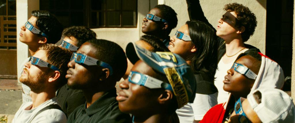 Cena do filme Edifício Gagarine. A imagem mostra um grupo de jovens de diferentes etnias, todos voltados para o lado esquerdo, olhando para cima. Eles usam óculos iguais, com as cores azul, branco e preto.