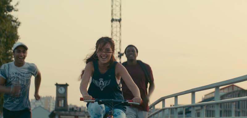 Cena do filme Edifício Gagarine. A imagem mostra uma adolescente negra de pele clara andando de bicicleta em uma ponte, e dois jovens correndo atrás, um negro de pele clara à esquerda, outro de pele escura à direita. Os três sorriem. Ela usa camiseta regata e brincos de argola e tem cabelos ruivos. O jovem da esquerda usa boné e uma camiseta azul e branca. O da direita usa uma camiseta cor-de-vinho e uma mochila nas costas. Ao fundo são vistos um guindaste, uma torre com um relógio e o céu alaranjado do fim da tarde.
