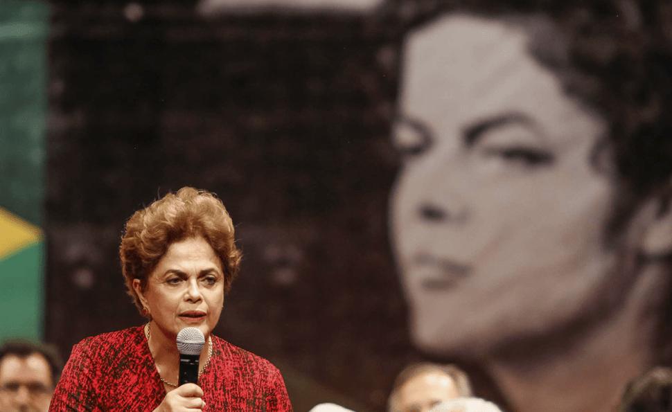 Cena do filme O Processo. A imagem mostra Dilma Rousseff no canto inferior esquerdo. Ela veste uma blusa vermelha e segura um microfone com a mão esquerda, enquanto olha para a frente e fala. Ao fundo, desfocada, existe uma imagem dela enquanto mais nova em preto e branco.