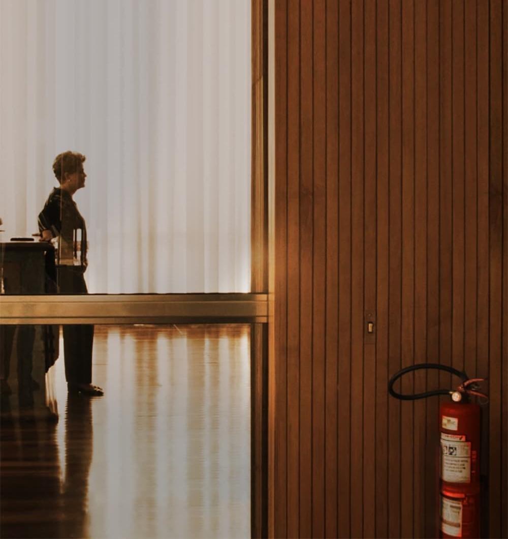 Cena do filme Alvorada. A imagem mostra Dilma Rousseff através de uma porta de vidro. Ela está caminhando, de lado, em direção ao lado direito da imagem, com pastas em baixo do braço. Atrás dela, existe uma cortina branca e à sua frente um painel de madeira ripada. No canto inferior direito, preso ao painel de madeira, existe um extintor de incêndio.