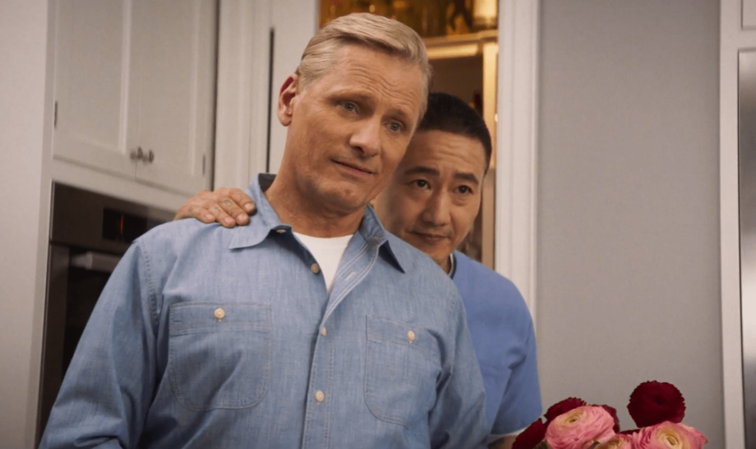 Cena do filme Ainda Há Tempo. Eric, um homem de pele amarela, está com a mão no ombro de John, seu marido, por trás. Eles estão na cozinha.