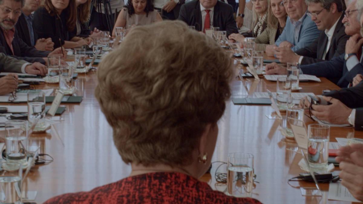 Cena do filme Alvorada. A imagem mostra a presidenta Dilma Rousseff de costas, numa mesa de reuniões repleta de pessoas. Dilma usa um blazer vermelho com desenhos pretos e olha para a frente, onde está a mesa. Todos olham para ela ao redor da mesa, onde existem vários copos de água, papéis e dispositivos eletrônicos.
