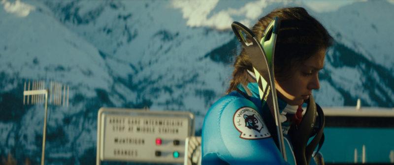 Cena do filme Slalom. No canto direito temos Lyz. Uma garota branca de cabelos lisos e pretos. Ela está de lado e veste um uniforme azul. Ela está segurando duas pranchas de esqui. O fundo é uma montanha com neve branca.