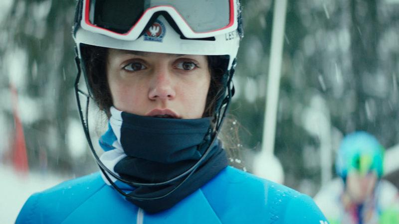 Cena de Slalom. Nela está Lyz. A garota usa um uniforme azul, capacete branco e óculos de proteção. Há também um pano preto em sua boca por conta do frio. O fundo é verde e desfocado. A aparência de Lyz é de assustada.