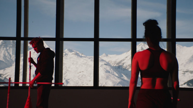 Cena do filme Slalom. À esquerda está o treinador. Um homem branco e de cabelos ruivos. À direita está Lyz de costas. O fundo é uma janela que mostra a paisagem de montanhas. Há uma luz vermelha em toda a cena.