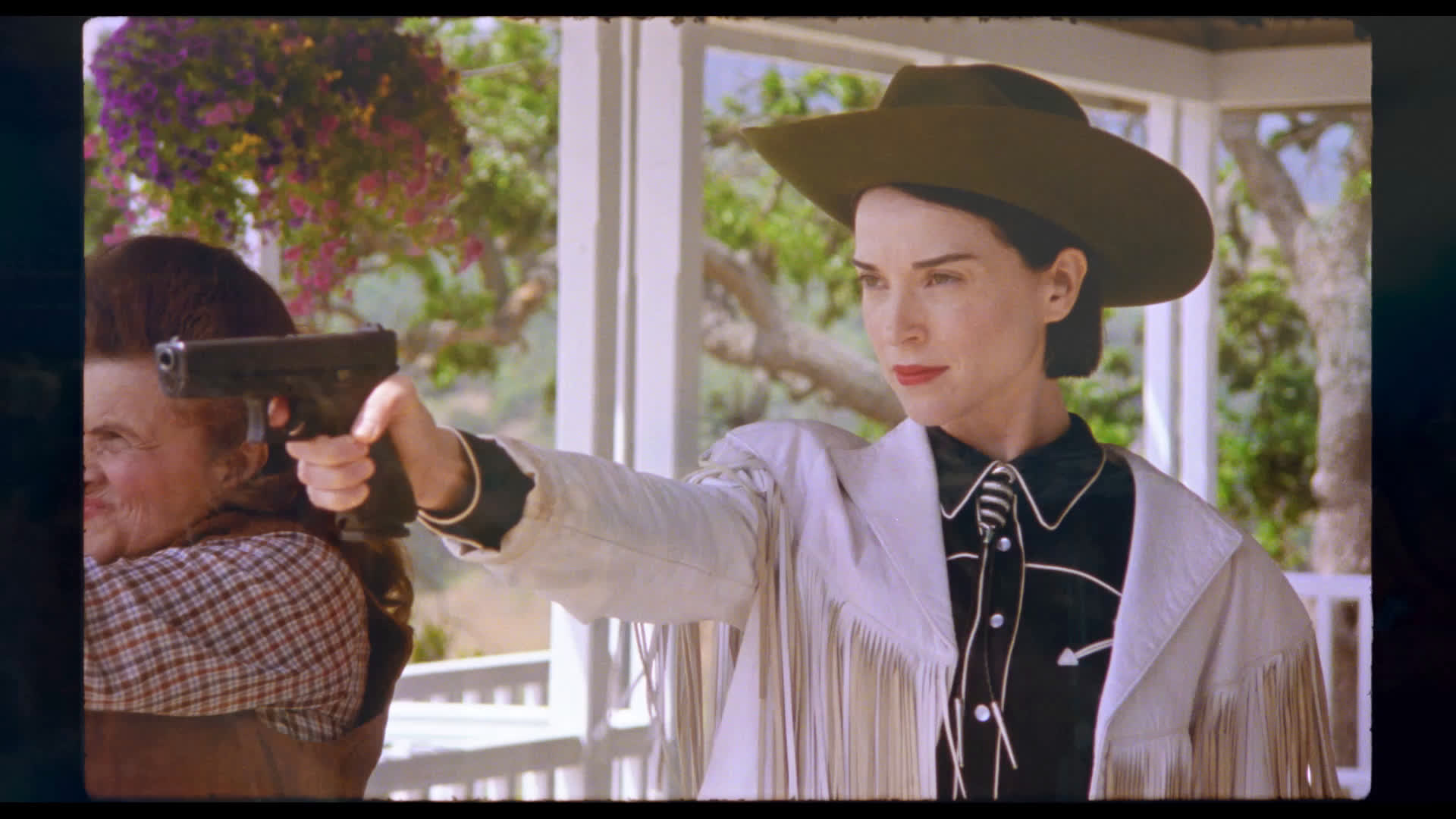 Cena do filme The Nowhere Inn. Fotografia em modo paisagem, com bordas laterais pretas. Em plano médio está Annie Clark com uma pistola apontada para frente. Annie é uma mulher branca, de aproximadamente 35 anos, olhos verdes e cabelo liso, curto e preto. Ela veste um chapéu de cowboy marrom, uma camisa preta, jaqueta de couro branca com franjas e usa batom vermelho. Ao lado está uma mulher idosa de aproximadamente 60 anos. No fundo está uma varanda branca com árvores.