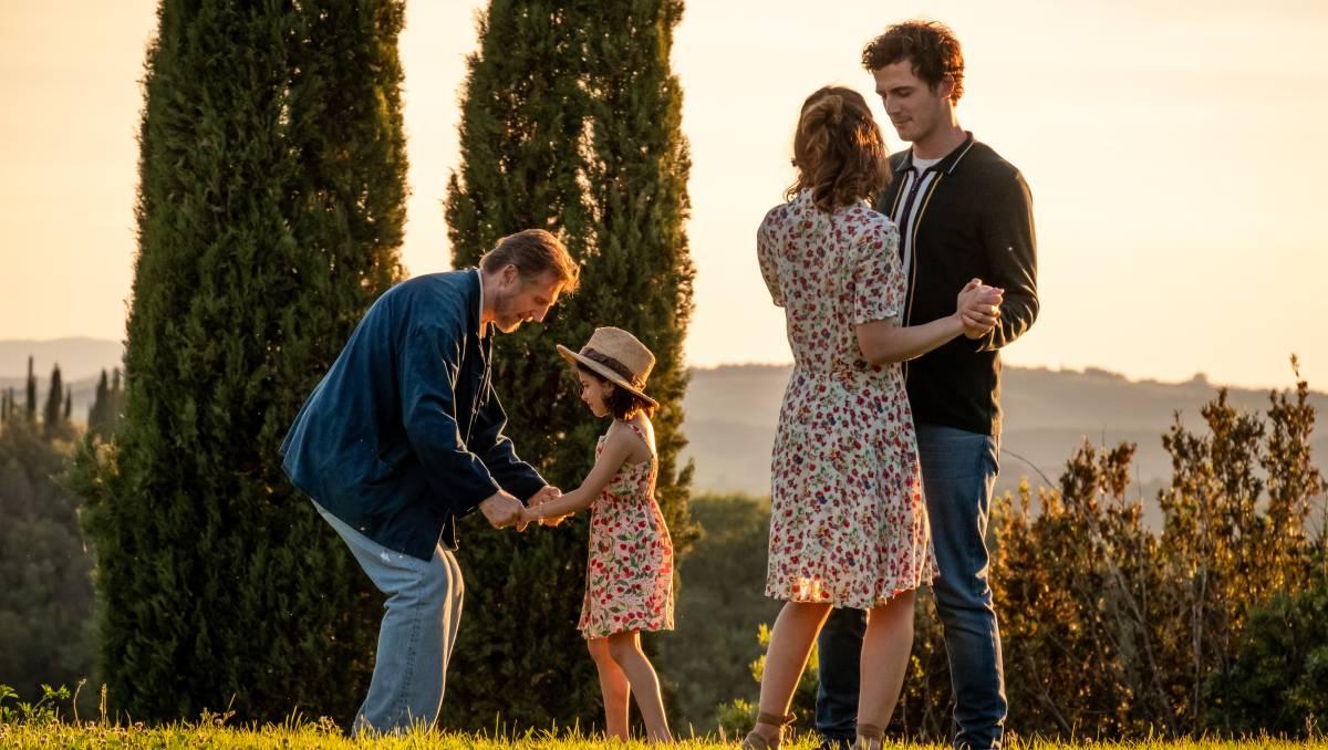 Cena do filme Made in Italy. A cena mostra 4 pessoas em um campo ensolarados: um idoso agachado com uma criança e um casal de adultos, todos brancos.