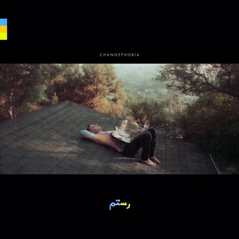 Capa do CD Changephobia, do cantor Rostam. A foto de capa mostra ele deitado em um telhado, está de dia e o fundo tem florestas