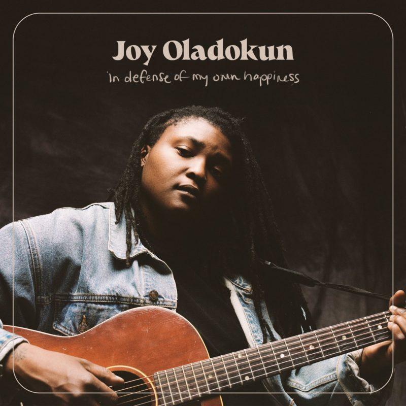 Capa do CD In Defense of My Own Happiness, da cantora Joy Oladokun, uma mulher negra, que está na foto de jaqueta jeans e tocando violão