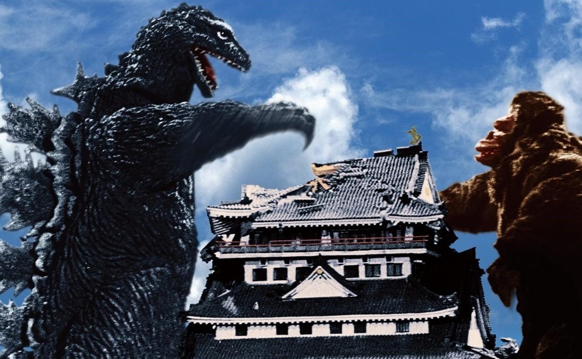 A imagem é retangular e mostra o antigo filme do King Kong vs Godzilla. No canto esquerdo tem o Godzilla, ele está de pé e é mostrado da cintura para cima, sua pele é enrugada, escamosa e com uma tonalidade de verde acinzentado, nas suas costas há protuberâncias triangulares permeadas por espinhos, seu focinho está aberto e é mais alongado, ele tem os olhos esbugalhados. Seu braço direito está levantado desferindo um ataque. No canto direito tem o King Kong, ele é mostrado da cintura para cima. Sua pelagem é marrom, cobrindo todo o corpo, com exceção das mãos e do rosto. Na parte central da imagem tem uma casa de arquitetura japonesa, ela tem três andares e 6 janelas em cada um, tem telhado triangular e côncavo. As paredes são brancas e o telhado azul. A casa tem uma parte do telhado destruída por causa de um golpe do Godzilla. O fundo é um céu azul com nuvens.