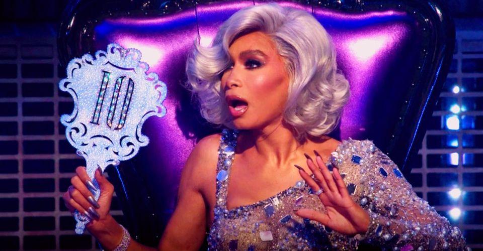 Cena de Legendary. A cena mostra Leiomy, uma mulher negra e magra, de peruca branca, com cara de surpresa e segurando uma placa com o número 10.