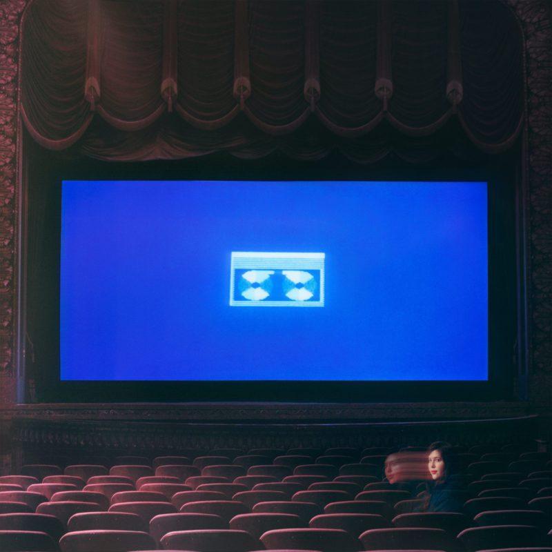 Capa do CD Home Video, da cantora Lucy Dacus. A imagem mostra uma tela de cinema, com um desenho de fita cassete em fundo azul. Nos bancos do cinema, está Lucy, com o rosto sombreado e enigmático.