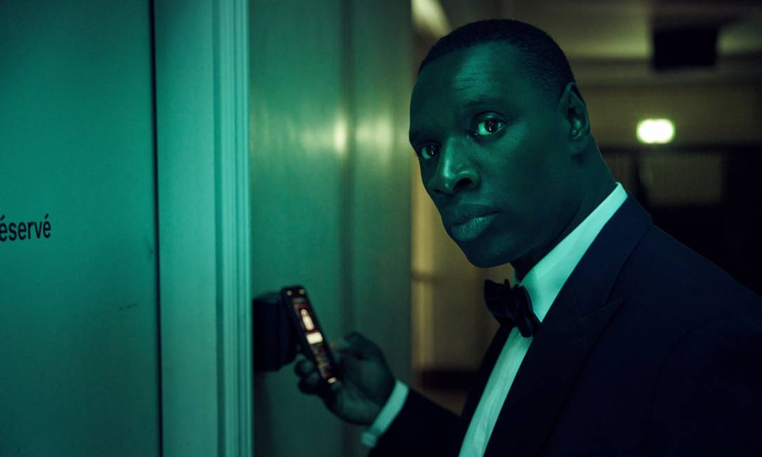 Cena da série Lupin. Assane (Omar Sy) vestido com um smoking preto e gravata borboleta, olha para os lados enquanto coloca um celular na frente de um dispositivo que tranca a porta na sua frente. Na tela desfocada do celular, vemos um cadeado fechado. Uma luz verde preenche a cena. Atrás de Assane, vemos um corredor que dá até uma porta com um sinal verde luminoso acima.