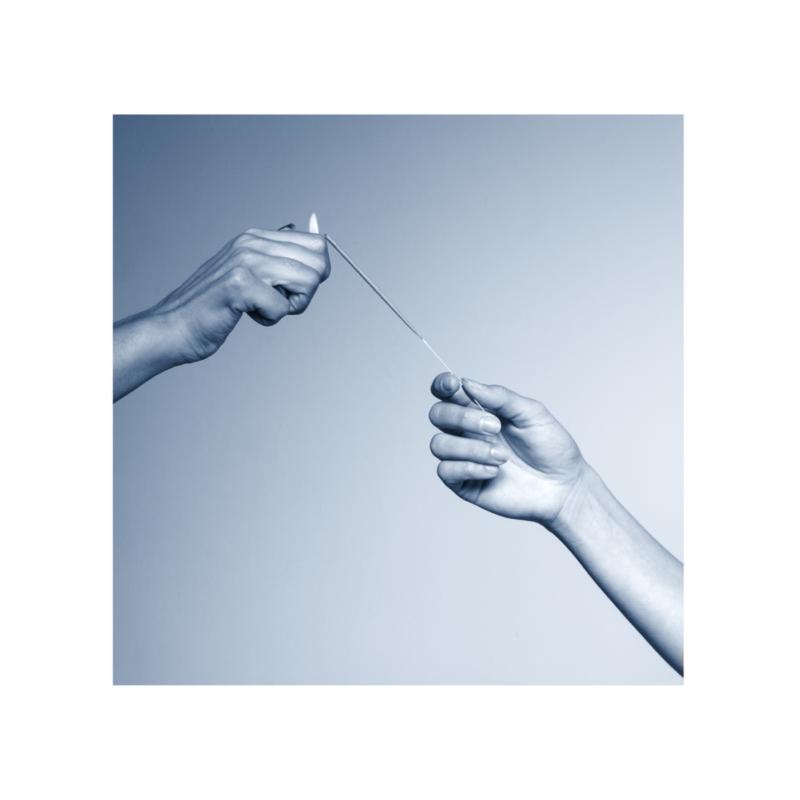 Capa do CD Esperança, da cantora Mallu Magalhães. A foto mostra duas mãos brancas segurando um pavio e uma chama. A cor é cinza e existe um quadro branco ao redor da imagem