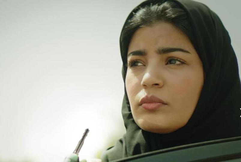Foto do filme A Candidata Perfeita. Nela está Mila Al Zahrani, atriz marrom usando hijab prert. A mulher está olhando para a esquerda cm uma expressão preocupada. Na sua mão está uma chave e uma parte da porta de um carro. O fundo é um céu azul.