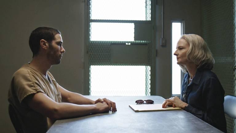 Cena do filme O Mauritano. Da esquerda para a direita na imagem, sentados frente a frente à mesa de uma sala de interrogatórios de uma prisão, vemos Mohamedou, interpretado por Tahar Rahim, um homem de ascendência muçulmana, de cabelos e barba castanhos curtos, aparentando ter cerca de 30 anos, vestindo um uniforme bege de prisioneiro, e Nancy, interpretada por Jodie Foster, uma mulher branca, de cabelos grisalhos lisos na altura do ombro, aparentando ter cerca de 60 anos, vestindo uma camisa social preta e com um envelope em sua frente.