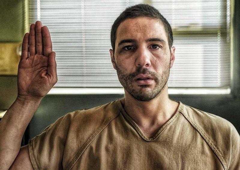 Cena do filme O Mauritano. Ao centro, Mohamedou Slahi, interpretado por Tahar Rahim, um homem de ascendência muçulmana, com cabelos e barba castanhos curtos, aparentando ter cerca de 30 anos, veste um uniforme bege de prisioneiro e tem sua mão direita levantada, em um juramento.