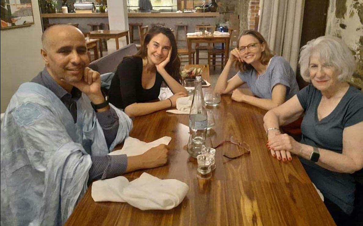 Foto dos bastidores do filme O Mauritano. Na foto, sentados à uma mesa de madeira e sorrindo para a câmera, vemos, à esquerda, Mohamedou Slahi, um homem muçulmano, careca, aparentando ter cerca de 40 anos, vestindo uma camisa e um xale azuis; a atriz Shailene Woodley, uma mulher branca, de cabelos castanhos lisos e longos, aparentando cerca de 30 anos, vestindo uma camiseta preta; à direita, a atriz Jodie Foster, uma mulher branca, de cabelos loiros e lisos na altura do ombro, aparentando ter cerca de 60 anos, vestindo uma camiseta azul e óculos pretos; e Nancy Hollander, uma mulher branca, de cabelos brancos lisos na altura do ombro, aparentando ter cerca de 80 anos, vestindo uma camiseta cinza.
